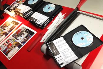 Die Covers werden zugeschnitten auf das Format der Boxen. Stück für Stück werden Datenträger gebrannt, beschriftet und eingelegt.